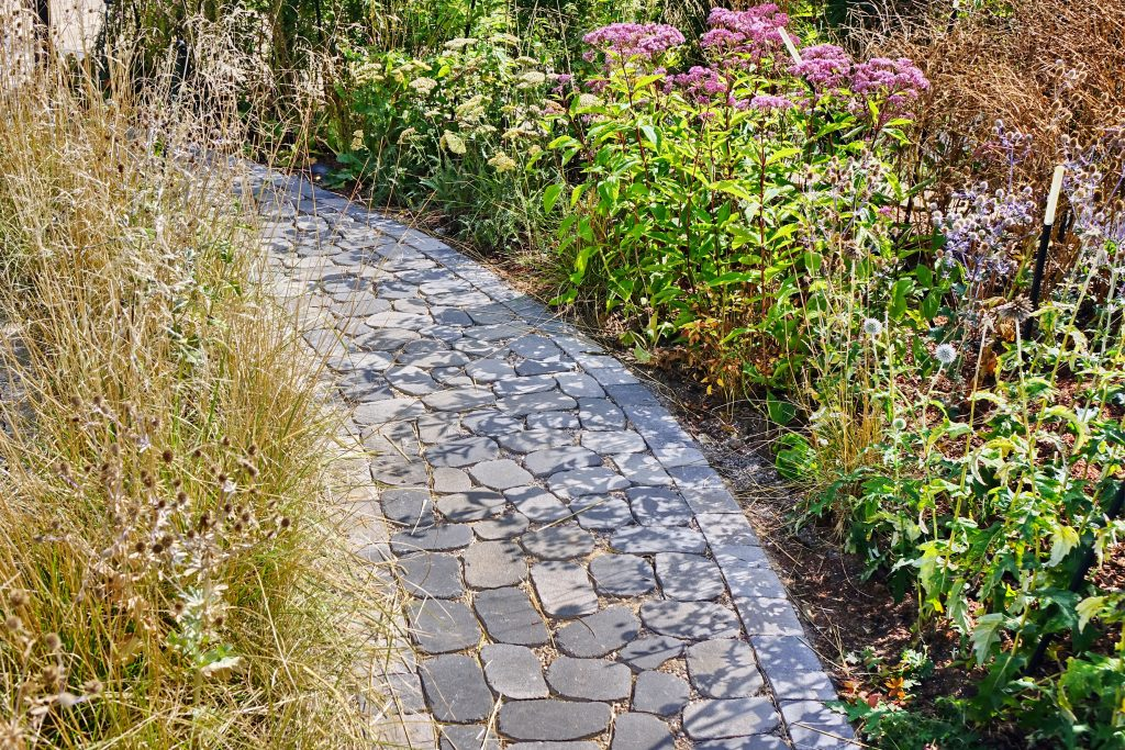 pathway with granite pavers flanked by garden flowers