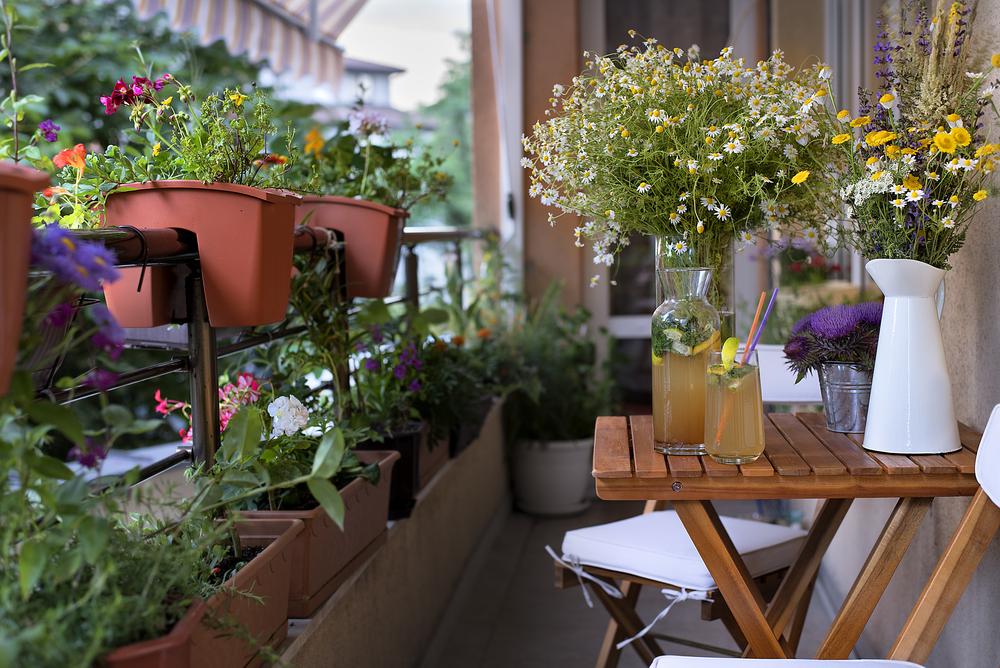 a balcony garden with patio furniture