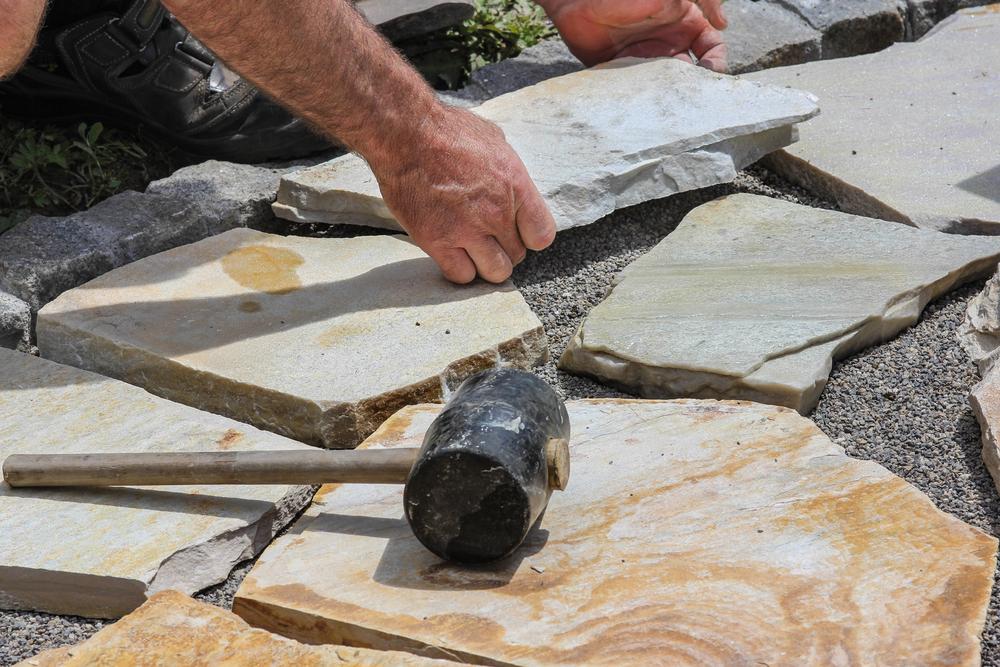 man installs marble pavers